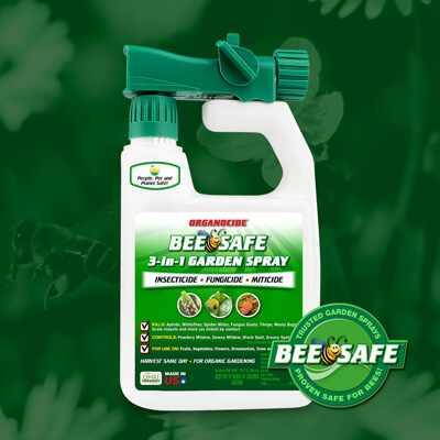 green and white 32 ounce spray nozzle container of bee safe organic pest garden spray over green flower field